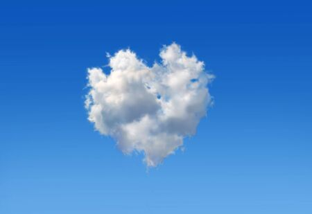 Fluffy cloud with the shape of a heart in a blue sky as love sign.