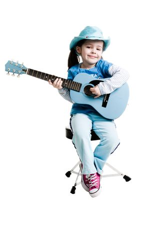 children acting: Young girl playing on a guitar while sitting on a white background Stock Photo