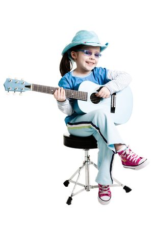 Young girl playing on a guitar while sitting on a white background photo