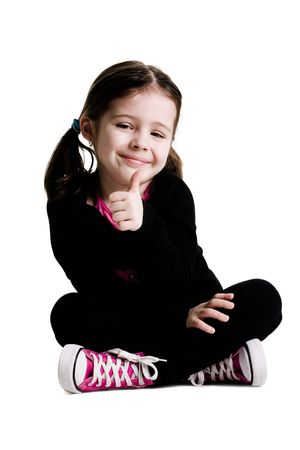 children acting: Young girl sitting with legs crossed and giving a thumbs up on a white background