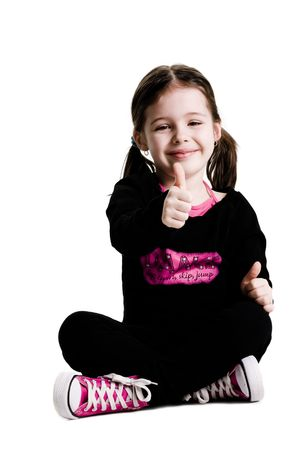Young girl sitting with legs crossed and giving a thumbs up on a white background Banco de Imagens - 2764568