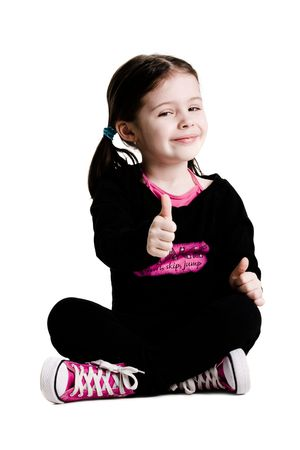 Young girl sitting with legs crossed and giving a thumbs up on a white background