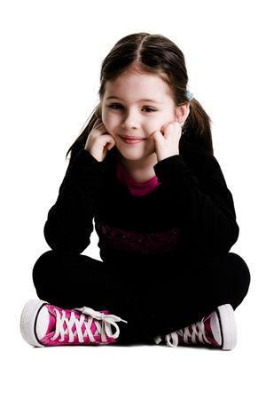 Young girl sitting with legs crossed on a white background