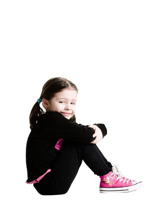 hugging legs: Young girl sitting while hugging legs out on a white background