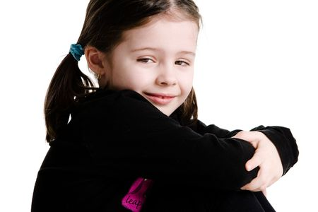 hugging legs: Close up of a young girl sitting while hugging legs out on a white background Stock Photo