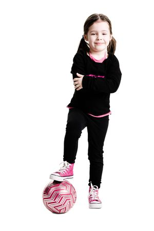 Young girl standing while putting her foot on a soccer ball on a white background Banco de Imagens