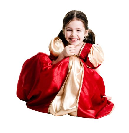 Young girl wearing a red dress crouching down on a white background