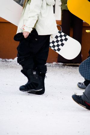 black ski pants: A person walking and carrying their snowboard Stock Photo