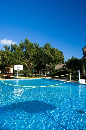 Swimming pool with a volleyball net at a resort in the tropics