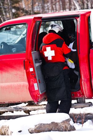 A rescue patrol officer pulling something out of the vehicle at a ski resort