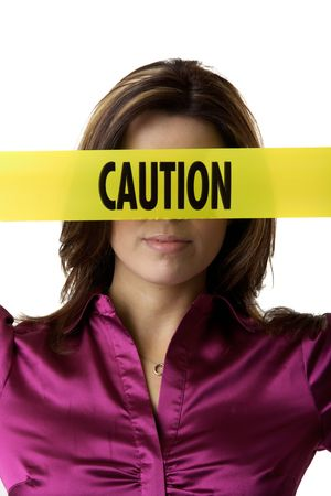 Brunette holding yellow caution tape over eyes and nose photo