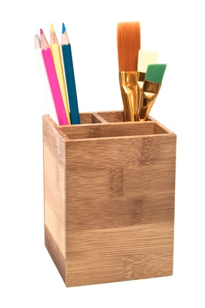 Colorful pencils and paint brushs in wooden holder isolated on white