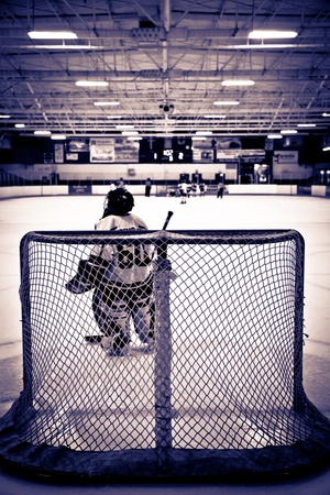 Young ice hockey goalie waiting in net Editorial
