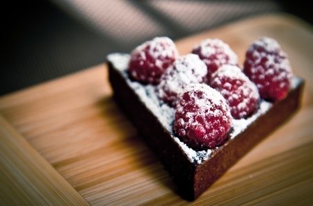 Chocolate Cake with Raspberries over on Wood Plate Banco de Imagens