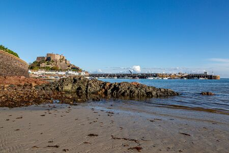 A view of Gorey harbour and castle on the island of Jersey, on a sunny day