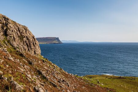 The coastline at Neist Point on the western side of the Isle of Skye, with a blue sky overhead