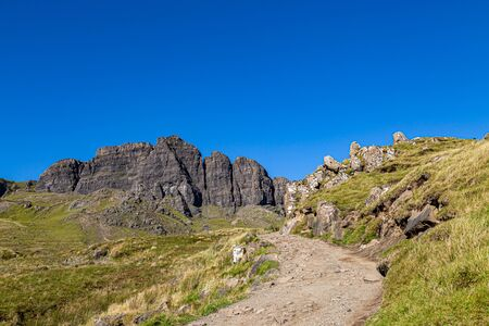 A pathway leading to The Old Man of Storr on the Isle of Skye, with a blue sky overhead