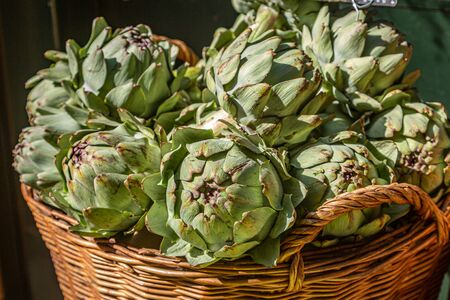 A basket of globe artichokes for sale at a farmers market