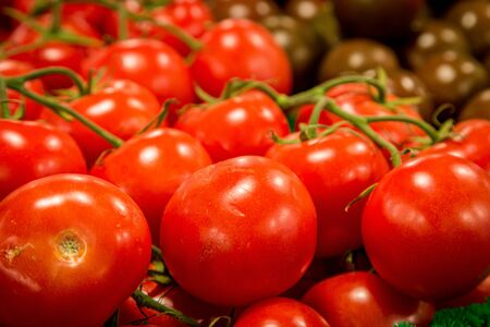 Bright red tomatoes on display at a farmers market stall