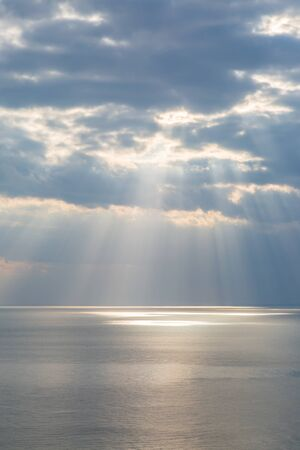Looking out over the ocean from the cliffs at Seaford, with sunlight shining through the clouds on the water Stock fotó