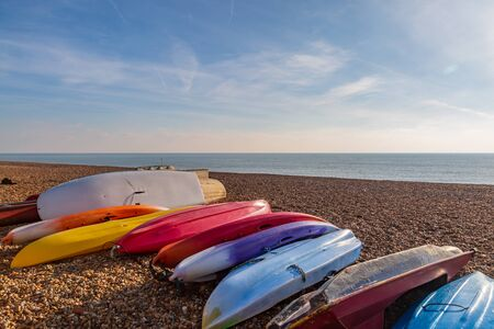 Kayaks laying on the pebble beach at Brighton, on a sunny winters day