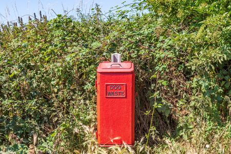A red dog waste bin in the Sussex countryside, surrounded by green foliage