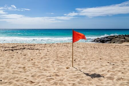 A red warning flag on a caribbean beach