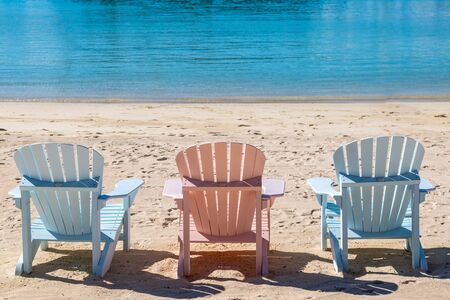 Three empty chairs on a sandy beach, on the island of Bermuda