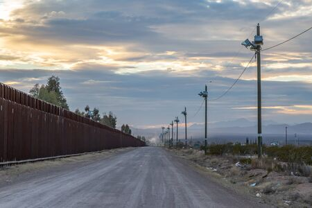 Looking along the road running alongside the US-Mexico border, at dusk