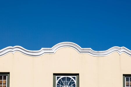 The decorative edge of a building in Cape Town, with a blue sky overhead