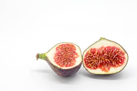A studio photograph of a fig cut in half, against a white background Banco de Imagens