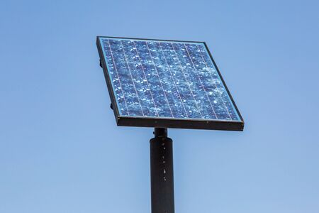A solar panel pointing towards the sun, with a clear blue sky behind Banque d'images