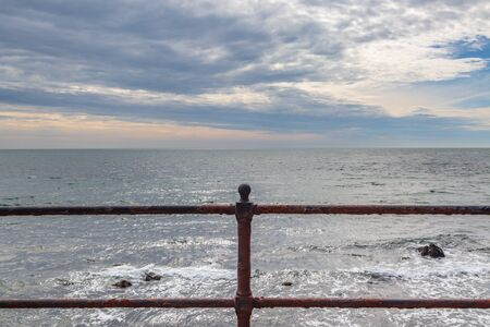 Looking out to sea over iron railings, at Ventnor on the Isle of Wight