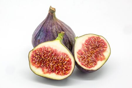 Two figs, one cut in half to show the seeds, against a white background