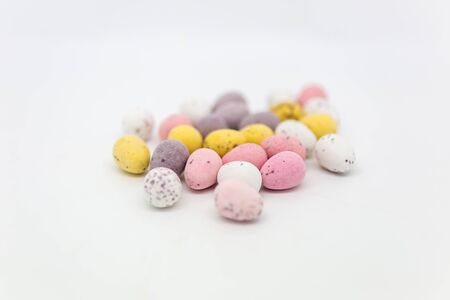 Small Easter eggs against a white background, with a shallow depth of field