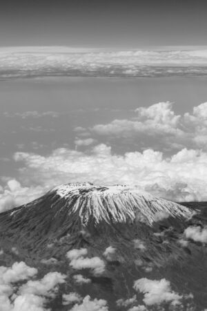 A vertical black and white photograph of   an aerial view of Mount Kilimanjaro