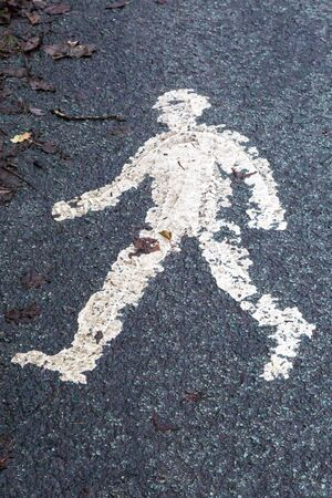 A photograph of a painted roadsign of a pedestrian