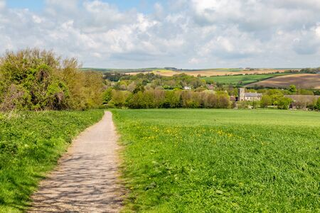 Looking towards Falmer Church in Sussex, with a patchwork landscape behind, on a sunny spring day