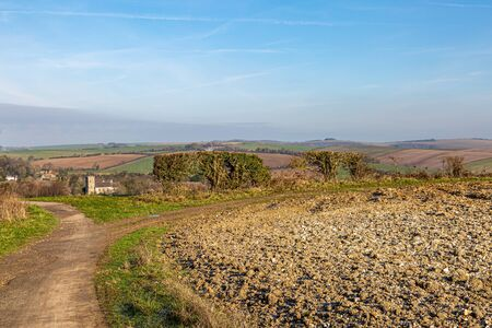 Looking along a pathway by farmland in Sussex on a sunny winters day, with the village of Falmer in the distance 版權商用圖片