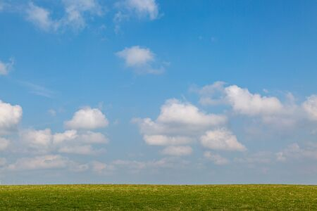 Blue sky and white clouds over a grass horizon