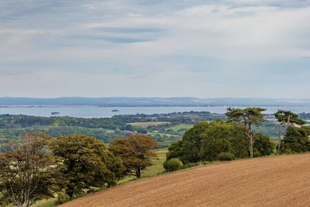 Looking out from a hilltop over farmland towards the coast, on the Isle of Wight