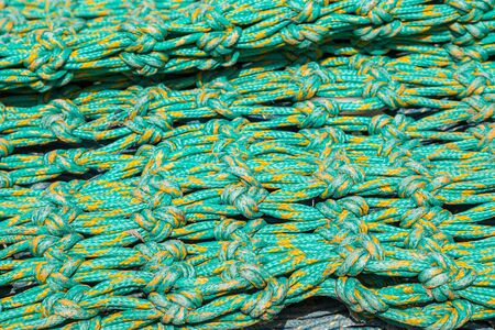A full frame photograph of a green and yellow knotted fishing net