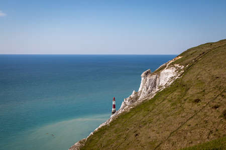 Looking out over the ocean at Beachy Head on the Sussex coast, with the lighthouse in the ocean beneath the cliffs and kayakers in the water