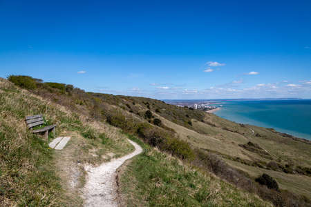 Looking along a coastal pathway on the Sussex coast with the town of Eastbourne in the distance Imagens