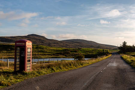 A rural road with a telephone box, on the Hebridean island of North Uist