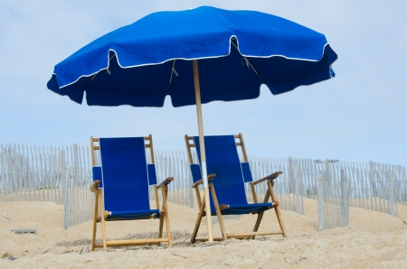 Two empty blue beach chairs and an umbrella