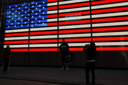 electronically: Tourists take photps at the electronically lit American Flag that dominates the scene in Times Square  Editorial