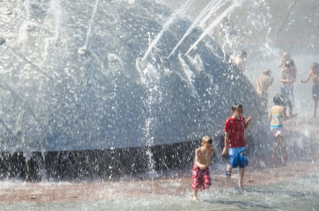 frolicking: Seattle, United States, August 6, 2013 - Close-up of children frolicking in the cool waters of the International Fountain on a sunny summer day