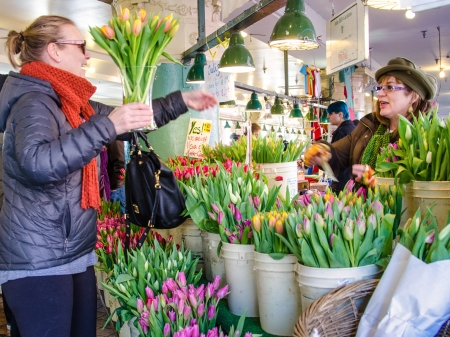 Seattle, United States - January 4, 2014 A young woman purchases flowers at Pike Place Market