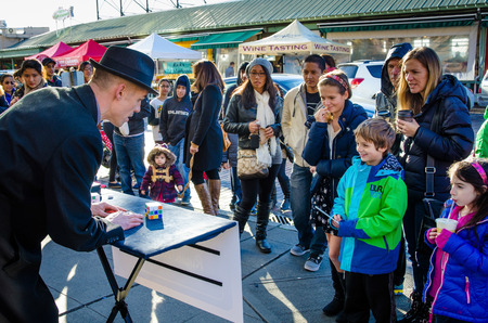 Seattle, United States, January 4, 2014 - A magician entertains a crowd across the street from the famous Pike Place Market